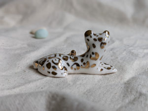 gold and porcelain snow leopard figurine